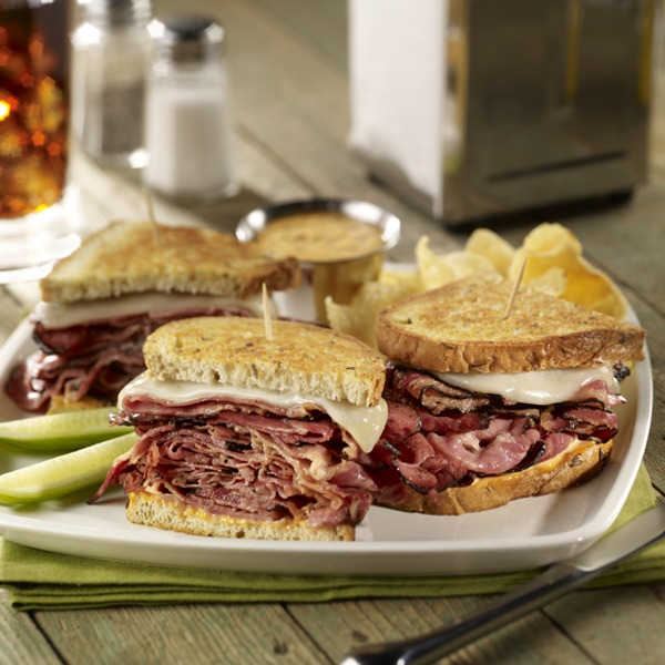 Sourdough pastrami melt sandwich on a plate with pickle spears
