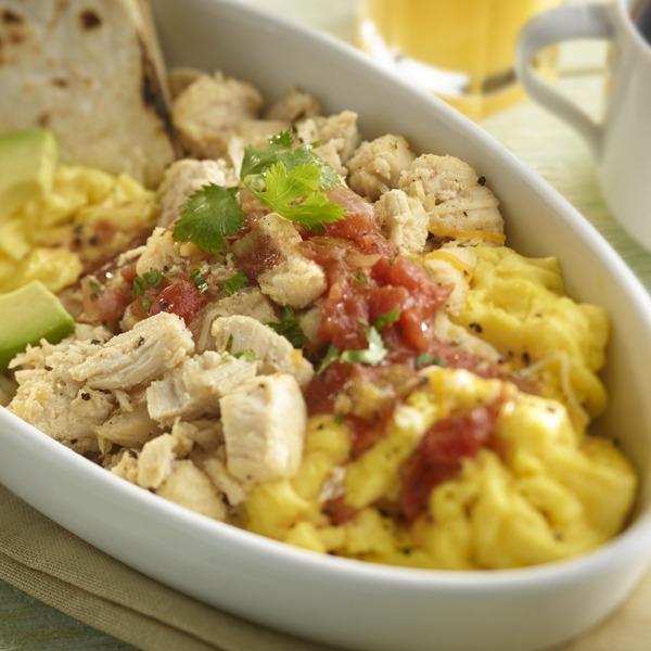Shredded chicken breakfast bowl with eggs, salsa, avocado, and tortilla