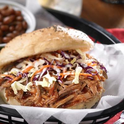 Carolina shredded pork and coleslaw sandwich in a basket with baked means