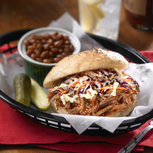 Carolina shredded pork and coleslaw sandwich in a basket with pickles and baked beans