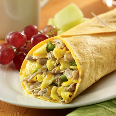Carnitas breakfast burrito on a plate with grapes and melon