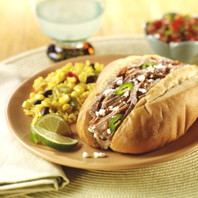 Shredded pork Mexican torta on a plate with corn and lime wedges