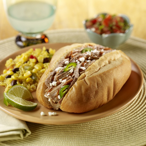 Shredded pork Mexican torta style sandwich on a plate with corn and lime wedges