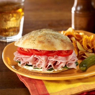 Ham dinger sandwich on a plate with pickles and chips