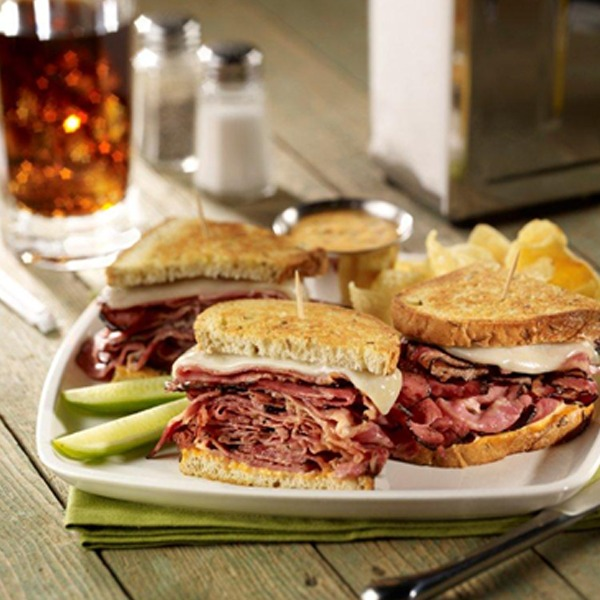 Sourdough sliced pastrami melt sandwich on a plate with pickle spears and potato chips