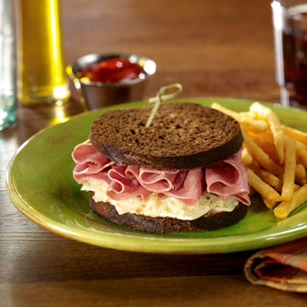 Corned beef deli delight sandwich on a plate with french fries