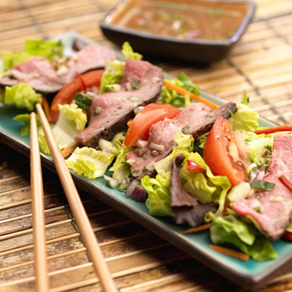 Thai peanut beef salad on a plate with chopsticks
