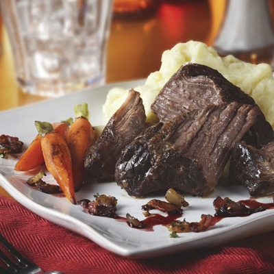 Braised pot roast bacon onion relish, carrots, and mashed potatoes on a plate