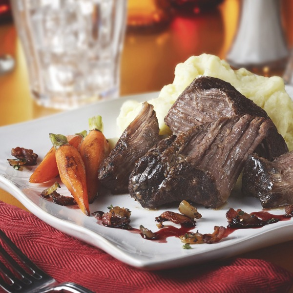Braised pot roast with bacon onion relish, carrots, and mashed potatoes on a plate