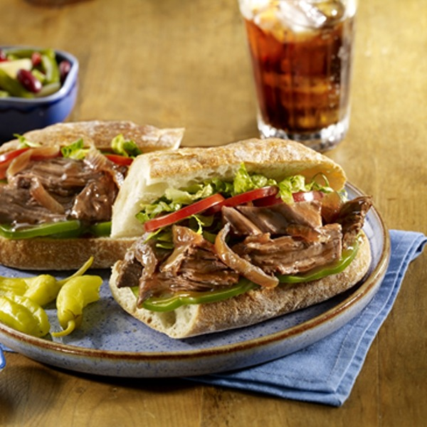 Pot roast po' boy on a plate with peppers and a glass of soda