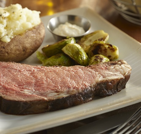 Prime rib with baked potato and brussel sprouts on a plate