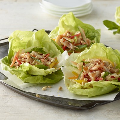 Three shredded tai chicken lettuce wraps on a plate